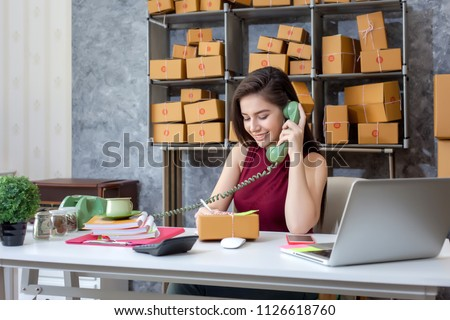 Selling products online. Portrait of a pretty woman phone talking to clients for shipping. Pack and delivery to the customer. #1126618760