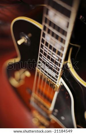 Semi-acoustic jazz electric guitar in closeup. Short depth of field