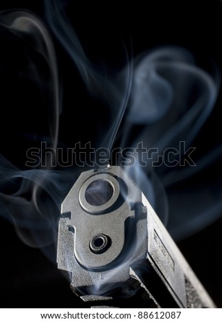 Semi-automatic handgun that is enveloped in smoke after a shot was taken