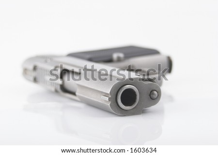 Semi automatic handgun with a matte silver finish laying on its side. Focus is on muzzle, with very shallow depth of field