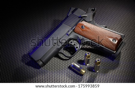Semi automatic handgun with blue lighting and three cartridges