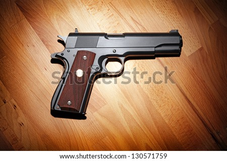 Semi-automatic M1911 Mark IV Series 80 .45 caliber pistol on the wooden table.