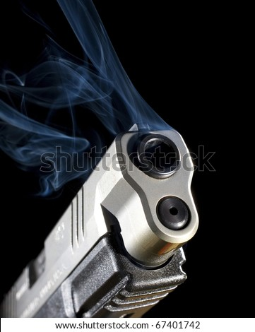 Semi-automatic pistol releasing smoke after a shot has been taken