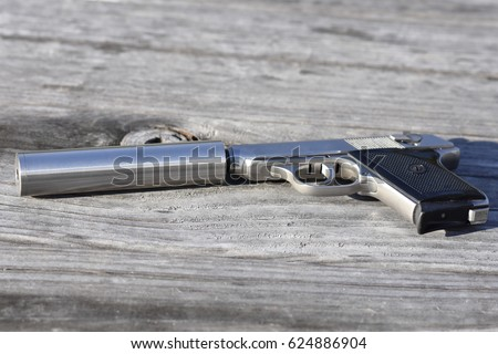 Semi-automatic pistol with silencer on wooden background #624886904