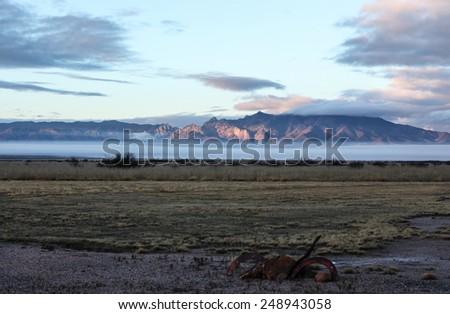 Semi-desert landscape with ground fog at sunlit mountains in winter morning/Pink Sunlight on Mountains with Baseline Ground Fog in Weather Landscape/Pink sunshine on mountains with low fog in winter