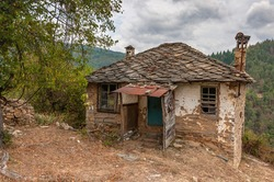 Semi-destroyed stone buildings in traditional Bulgarian style in the abandoned village of Dyadovtsi. Old stone adobe house with entrance shed and roof of stone slabs