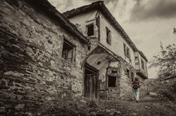 Semi-destroyed stone buildings in traditional Bulgarian style in the abandoned village of Dyadovtsi. Woman with a backpack and red blouse walking around an abandoned house and looking at an abandoned