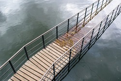 Semi-flooded walkway or bridge. Diagonal arrangement. Boards and metal structure with handrails. Glare and water pattern. Top view.