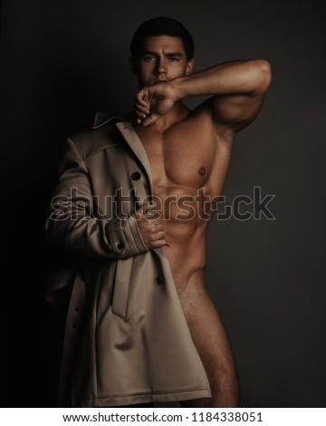 Semi-naked male fitness model in coat