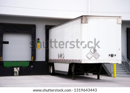 Semi trailer for freight in American logistic system big rigs semi trucks loading cargo at warehouse dock with thermally insulated gate to minimize temperature change of the load when loading #1319643443