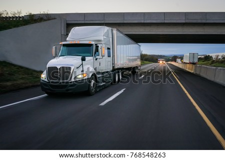 Semi-truck commercial vehicle 18 wheeler on highway with overpass