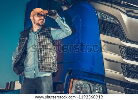 Semi Truck Driver and Hit Modern Vehicle. Happy Caucasian Trucker in His 30s. Transportation Industry. #1192560919
