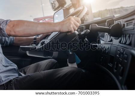 Semi Truck Driving Job. Caucasian Men Behind Semi Truck Steering Wheel. Cabin Interior. Transportation and Spedition Industry.