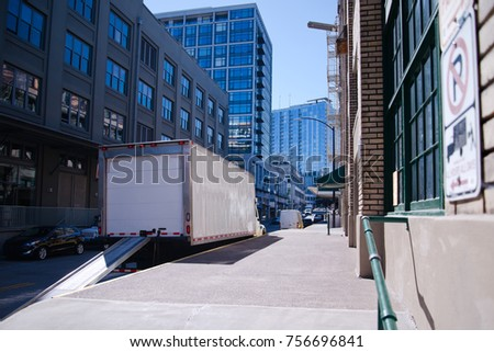 Semi Truck for delivery of goods in the city limit with a lowered gangway standing near the warehouse on the city street for loading or unloading goods for starting delivering