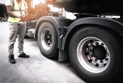 Semi truck, Maintenance and Vehicle inspection.  A truck mechanic driver holding clipboard, his safety checking a truck wheels and tires.