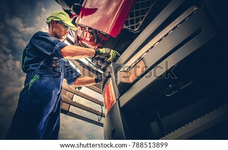 Semi Truck Maintenance. Caucasian Truck Service Worker in His 30s Performing Scheduled Recall Maintenance.