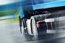 Semi Truck Spedition. Speeding Semi Truck on the Highway. Closeup Photo. Heavy Duty Transportation.