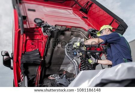 Semi Truck Under Maintenance. Caucasian Truck Mechanic Working to Fix the Tractor.