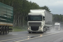 Semi trucks lorry convoy move on suburban wet asphalted highway front view on cloudy summer day, safety drive overtake on rain slippery road on green forest background
