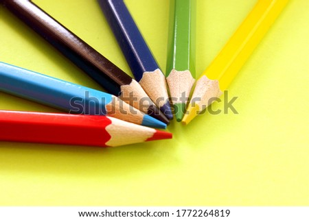 Semicircle of colored pencils on a yellow background. Lots of different colored pencils. Colored pencil. Pencils are sharp. Pencils lie in top left corner. Close-up. Copy space. Background. Flat lay