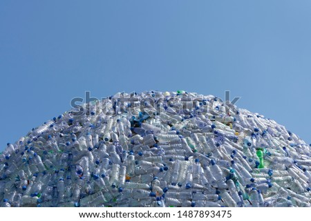 semicircular mountain of plastic waste, plastic bottles with a beautiful blue background