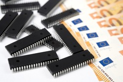 Semiconductor chips shortage and high price. Pile of computer chips and spread of Euro banknotes. Concept for crisis and deficit in the electronic industry.