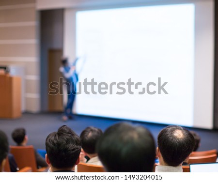 Seminar with expert speaker presenting to audience in hall. Blank business presentation screen for copy space. Executive presenter giving a speech. Leadership training coach in workshop lecture.  #1493204015