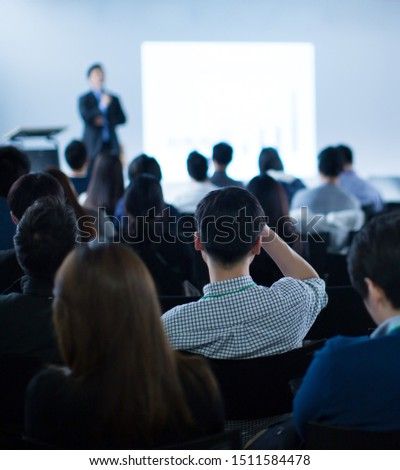 Seminar with expert speaker presenting to audience in hall. Blank business presentation screen for copy space. Executive presenter giving a speech. Leadership training coach in workshop lecture.  #1511584478