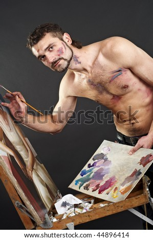 Seminude artist paints on an easel
