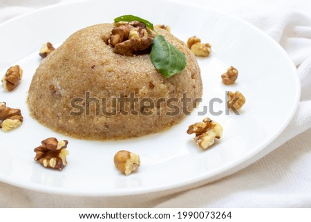 Semolina halva is a Turkish dessert obtained by roasting semolina with flour, sugar, oil (margarine or butter) and other additives such as pine nuts, water, milk if desired.Selective focus. Stock photo ©