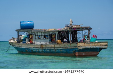Semporna Islands, Sabah/Borneo, Malaysia-May11, 2019:An old traditional house boat, in turquoise sea, is home to the namadic, sea gypsy people of the Semporna Island Park, Borneo, Malaysia. #1491277490