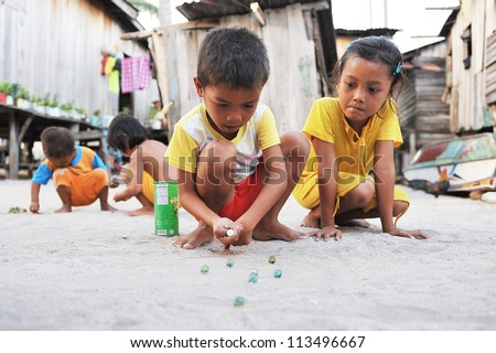 SEMPORNA, MALAYSIA - JULY 24 : Unidentified sea gypsies kids playing marbles on July 24, 2009 in Semporna, Sabah, Malaysia. Children here do not attend school for lack of means and resources.