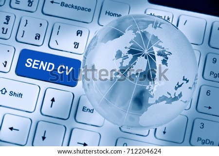 Send CV or curriculum vitae concept : Blue button on a white laptop computer keyboard inscribed or printed with words SEND CV, with a crystal clear globe and opaque world map. Vintage filter effect. #712204624