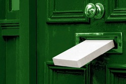 Sending a Gift In The Post.Postal box the parcel is delivered through the parcel door opening.White post box, old aged grunge green wooden door.Delivery of parcels during the period of self-isolation.