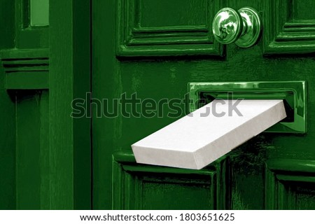 Sending a Gift In The Post.Postal box the parcel is delivered through the parcel door opening.White post box, old aged grunge green wooden door.Delivery of parcels during the period of self-isolation. Stock photo ©