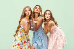 Sending air kiss. Three best friends posing in studio, wearing summer style dress against green background. Girls smiling and having fun. Studio shot on green background
