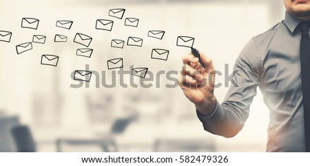 sending email concept - businessman drawing envelopes in office