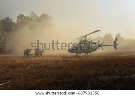 Sending injured soldiers back by helicopter. Group of elite unit combat soldiers carrying a wounded friend on a stretcher through a sandy terrain after a fierce battle against terrorists.