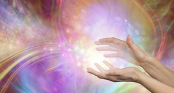 Sending you beautiful healing energy vibes - female cupped hands with white energy formation flowing outwards, sparkles and colours moving in all directions with copy space
