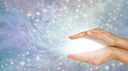 Sending you magical high frequency healing energy - female cupped hands with magical white plasma between flowing sparkles outwards on lilac energy field background with copy space