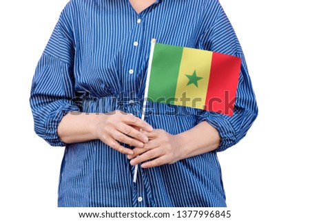 Senegal flag. Close up of woman's hands holding a national flag of Senegal isolated on white background. #1377996845