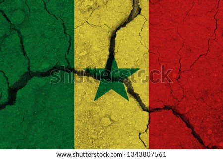 Senegal flag on the cracked earth. National flag of Senegal. Earthquake or drought concept #1343807561