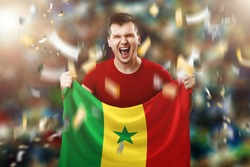 Senegalese fan, fan of a man holding the national flag of Senegal in his hands. Soccer fan in the stadium.