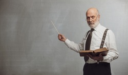 Senior academic professor giving a lecture and pointing at the empty blackboard using a stick: knowledge and traditional education concept