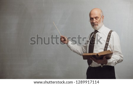 Senior academic professor giving a lecture and pointing at the empty blackboard using a stick: knowledge and traditional education concept Foto stock ©