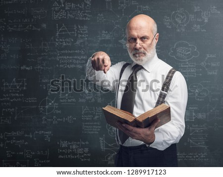 Senior academic professor holding a book and pointing at camera: exams and traditional education concept ストックフォト ©