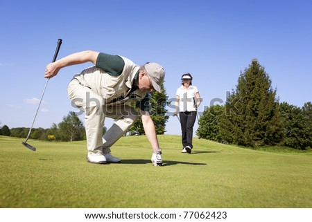 Senior active male golf player picking up golf ball from hole on green with female golf player walking in background with fantastic blue sky.