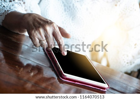 Senior adult aging retire elderly woman chat texting with friend, family, play game, reading on dining table relax and socialize using tablet, internet online digital technology to communicate
