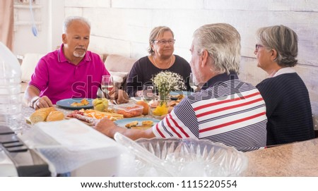senior adult at home have lunch together in friendship and happiness. all serious speaking about problems and issues. two women and two men for two families enjoy time in relationship #1115220554