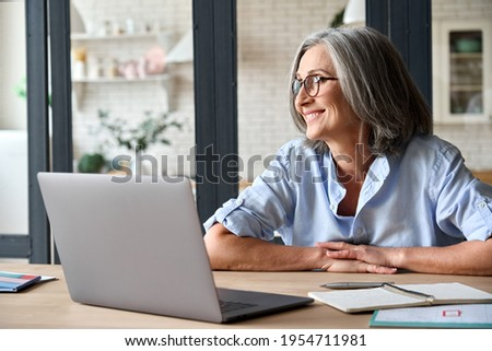 Senior adult mid 50s age watching at window at home sitting at table with laptop. Feeling happy and smiling to thoughts about future positive vision of successful training career after learning.